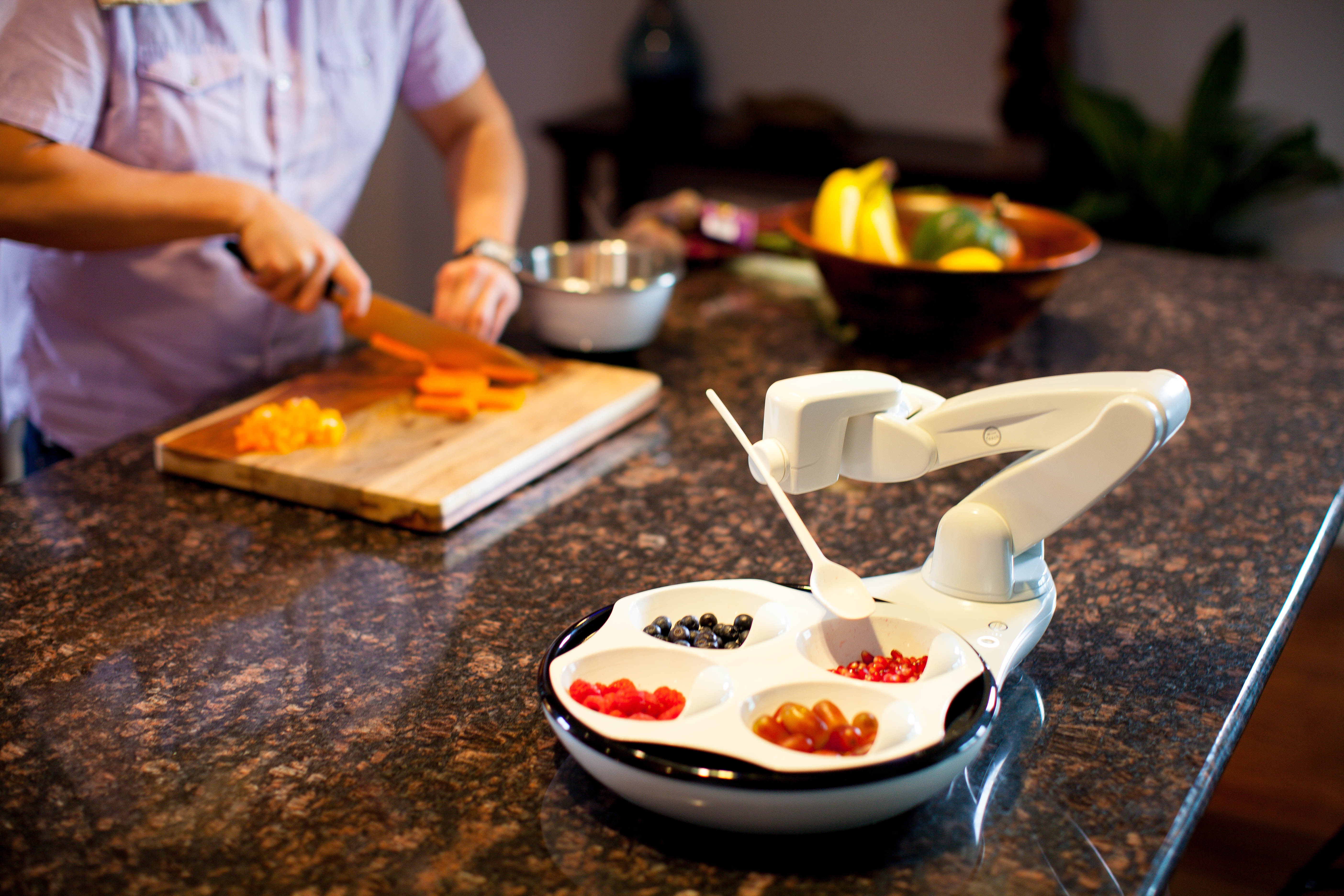 Snapshot of the Obi self feeder from the front shows the arm and spoon in position over the plate.