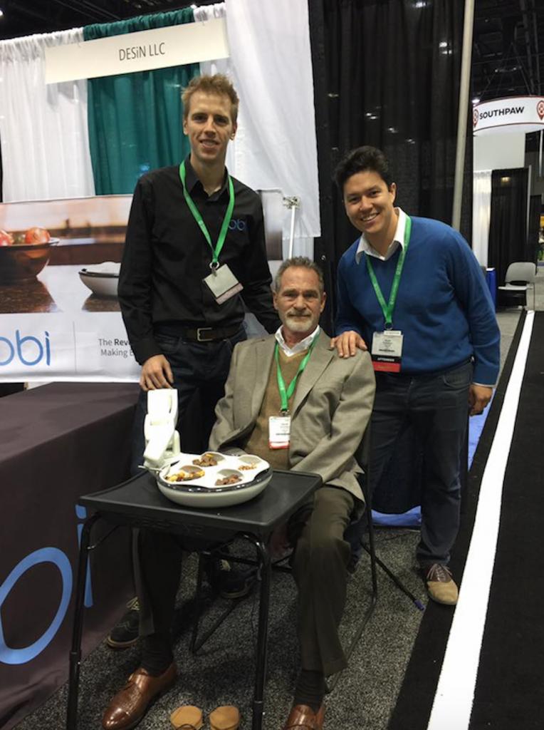 Obi team demonstrates their robotic feeding device at the AOTA Expo.